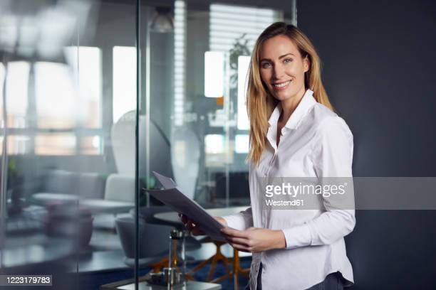 portrait of confident businesswoman holding papers in office - blouse stock pictures, royalty-free photos & images