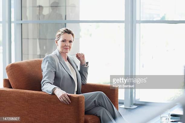 Portrait of confident businesswoman in armchair