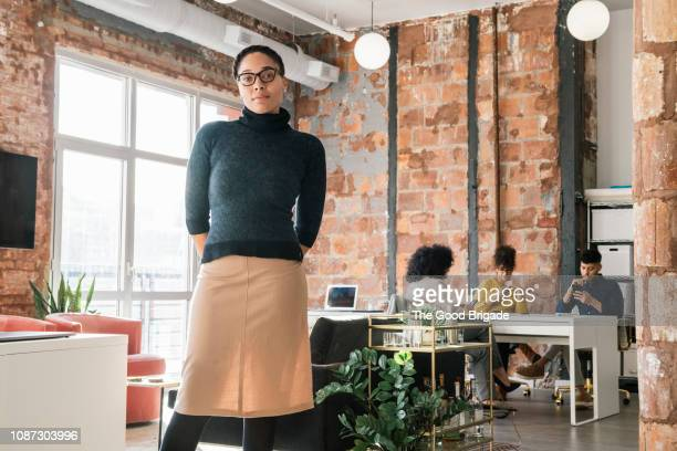 portrait of confident businesswoman in creative office - mensen op de achtergrond stockfoto's en -beelden