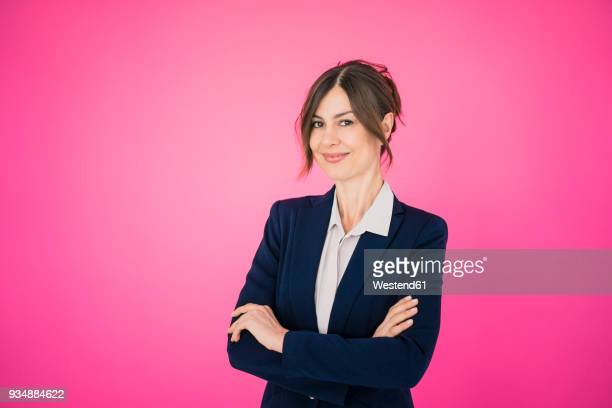 portrait of confident businesswoman in front of pink wall - pink background stock pictures, royalty-free photos & images