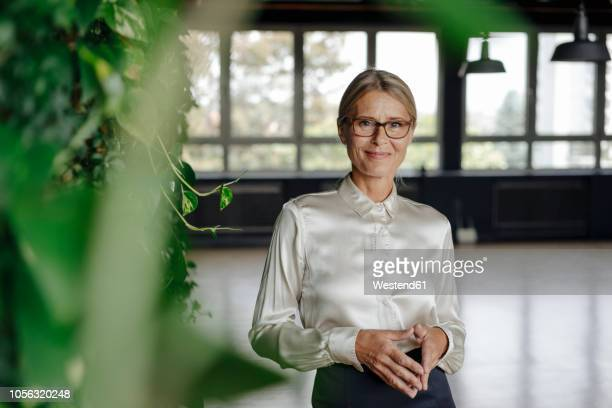 portrait of confident businesswoman in green office - directrice photos et images de collection