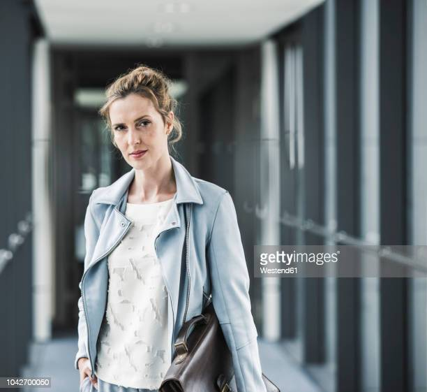 portrait of confident businesswoman in office passageway - cadrage à la taille photos et images de collection