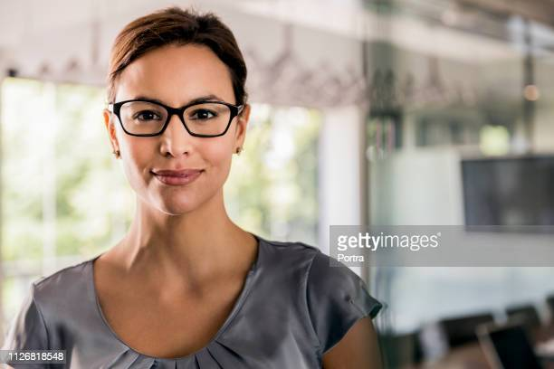 portrait of confident businesswoman in office - hair back stock pictures, royalty-free photos & images