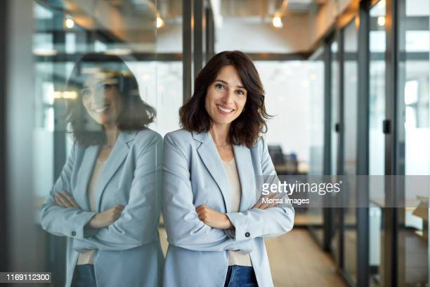portrait of confident businesswoman in office - bürokleidung stock-fotos und bilder