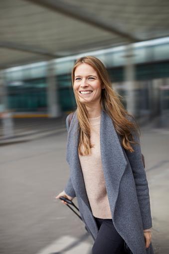 Portrait of confident businesswoman pulling suitcase at airport - gettyimageskorea