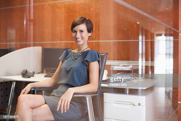 Portrait of confident businesswoman sitting at desk in office