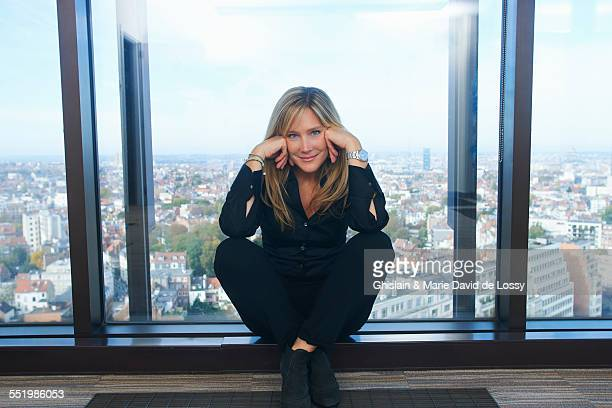 Portrait of confident businesswoman sitting in front of office window with Brussels cityscape, Belgium