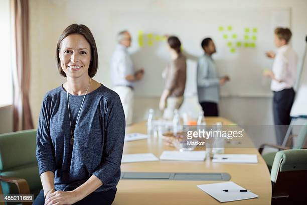 Portrait of confident businesswoman sitting on conference table with colleagues discussing in background