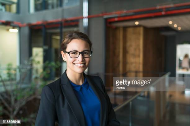 portrait of confident businesswoman smiling in office - 30 39 years stock pictures, royalty-free photos & images