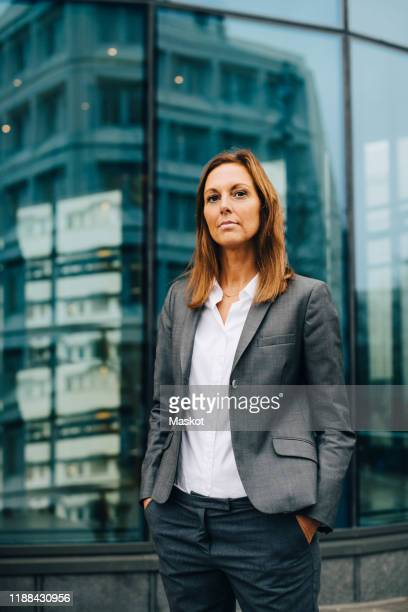 portrait of confident businesswoman standing against reflection on glass building - three quarter length stock pictures, royalty-free photos & images