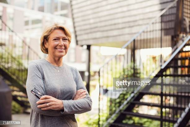 Portrait of confident businesswoman standing arms crossed at office yard