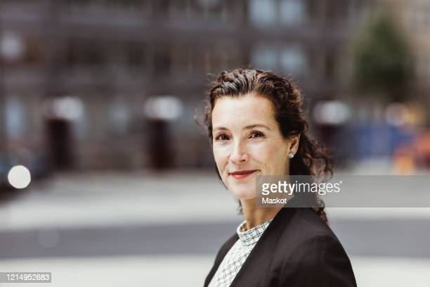 portrait of confident businesswoman standing outdoors - directrice photos et images de collection