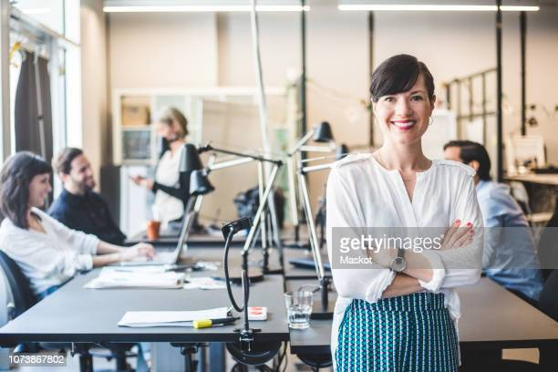 portrait of confident businesswoman standing with arms crossed against desk - angle poise lamp stock pictures, royalty-free photos & images