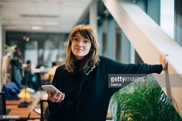 Portrait of confident businesswoman standing with smart phone in office
