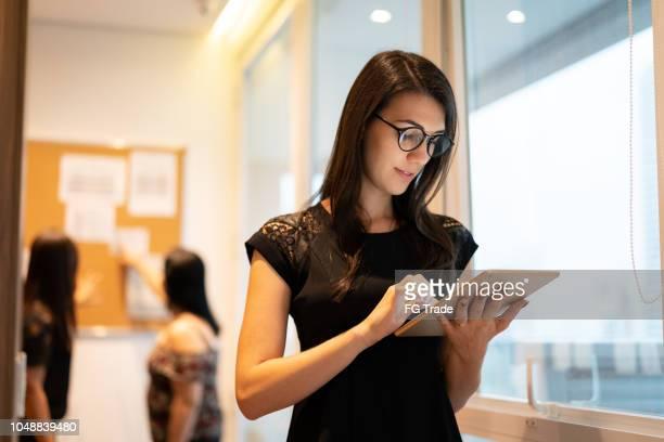 retrato de mulher de negócios confiante usando tablet no escritório - 25 30 anos - fotografias e filmes do acervo