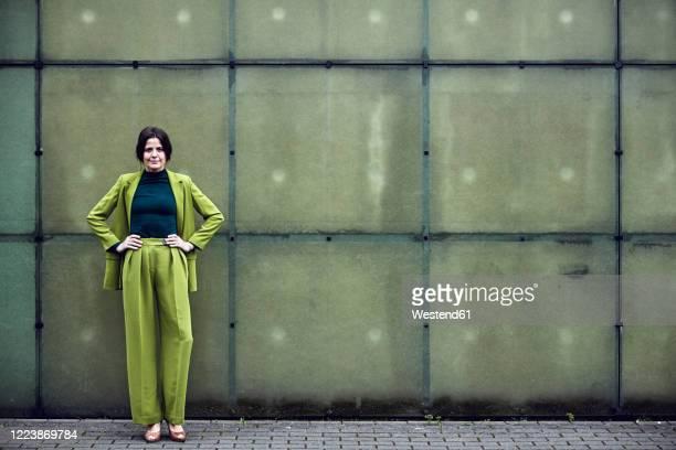 portrait of confident businesswoman wearing green suit standing at a wall - weibliche führungskraft stock-fotos und bilder