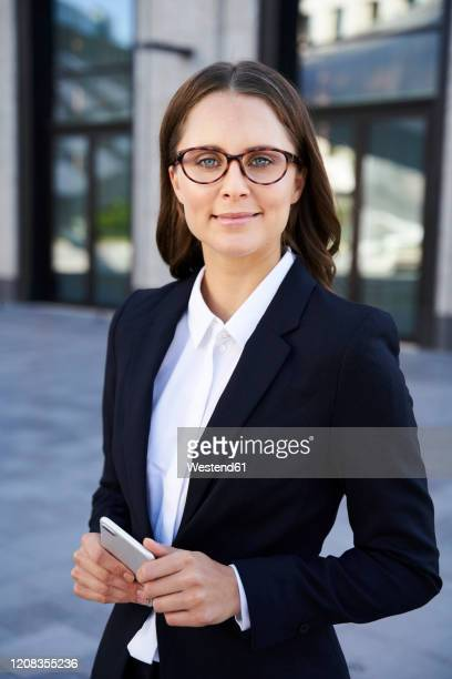 portrait of confident businesswoman with cell phone in the city - veste noire photos et images de collection