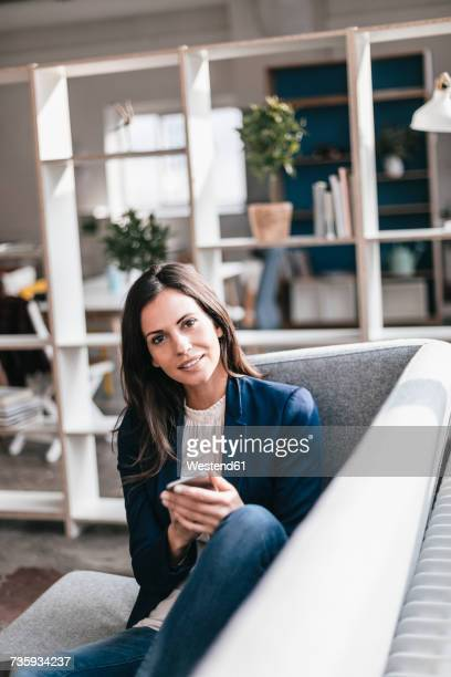 Portrait of confident businesswoman with cell phone on couch