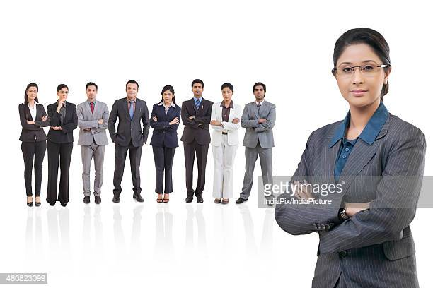 Portrait of confident businesswoman with colleagues against white background