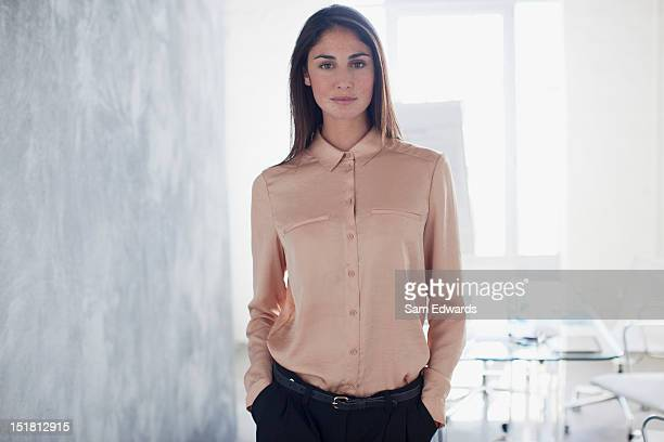 portrait of confident businesswoman with hands in pockets - serio fotografías e imágenes de stock
