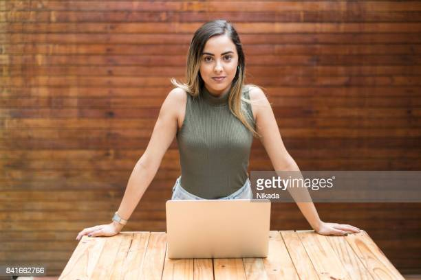 portrait of confident businesswoman with laptop at desk in creative office - sleeveless top stock pictures, royalty-free photos & images