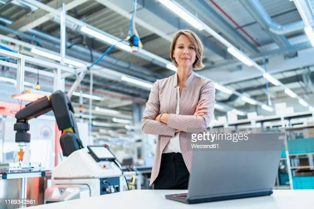 portrait of confident businesswoman with laptop in a modern factory hall - weibliche führungskraft stock-fotos und bilder