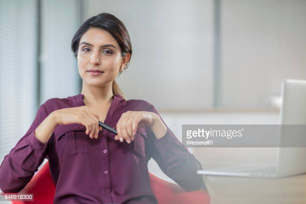 portrait of confident businesswoman with laptop in office - femme indienne photos et images de collection