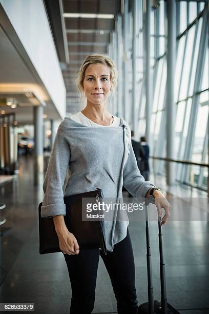 Portrait of confident businesswoman with luggage standing at airport