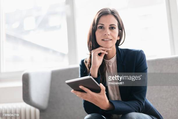 Portrait of confident businesswoman with tablet on couch