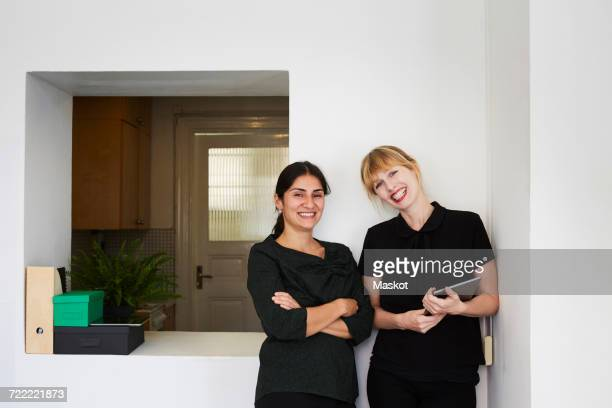 Portrait of confident businesswomen smiling in office