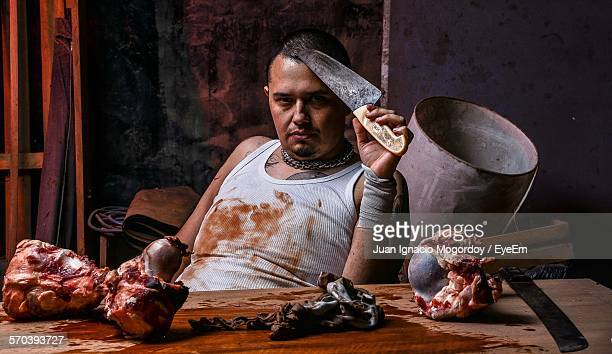 Portrait Of Confident Butcher Sitting In Front Of Meat On Table In Shop