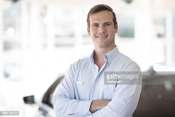 Portrait of confident car dealer in showroom