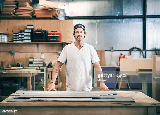 portrait of confident carpenter standing at workbench in workshop - schreiner stock-fotos und bilder