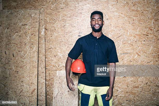Portrait of confident carpentry student holding hardhat while standing against wooden wall