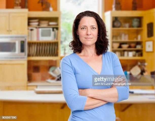 Portrait of confident Caucasian woman in domestic kitchen
