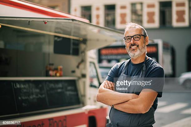 portrait of confident chef with arms crossed standing by food truck on street - happy merchant stock pictures, royalty-free photos & images