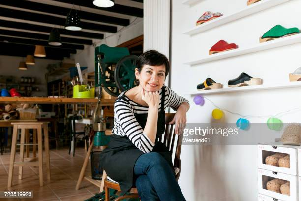 portrait of confident clogmaker in her workshop - shoe factory stock pictures, royalty-free photos & images