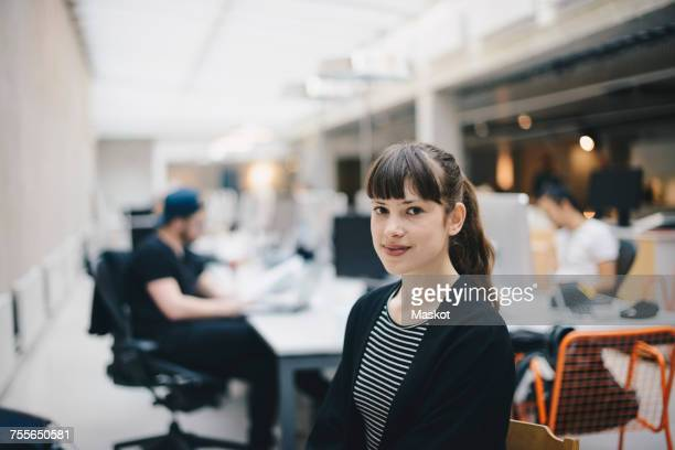 Portrait of confident computer programmer at office with colleagues working in background