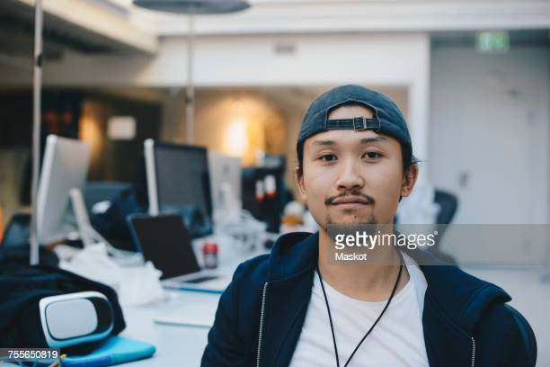 Portrait of confident computer programmer wearing cap in office