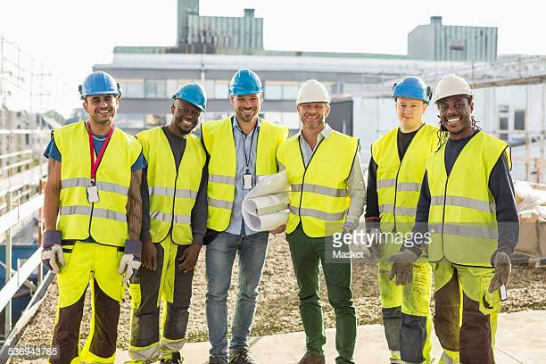 portrait of confident construction team standing together at site - medium group of people stock pictures, royalty-free photos & images