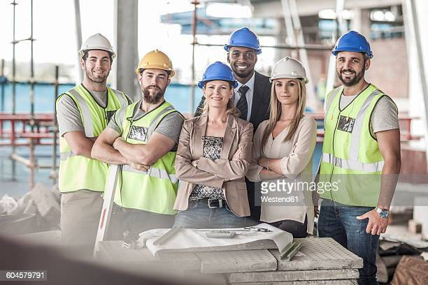 Portrait of confident construction workers and executives in construction site