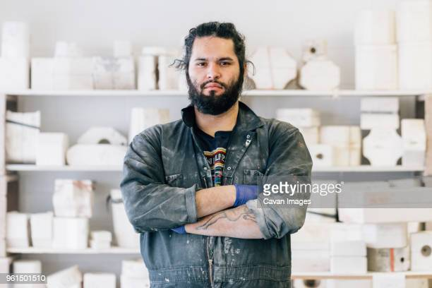 portrait of confident craftsman with arms crossed standing at workshop - ceramics stock pictures, royalty-free photos & images