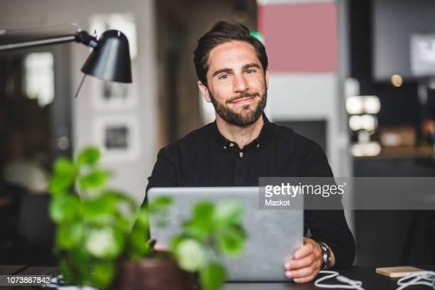portrait of confident creative businessman sitting at desk in office - 30 34 ans photos et images de collection