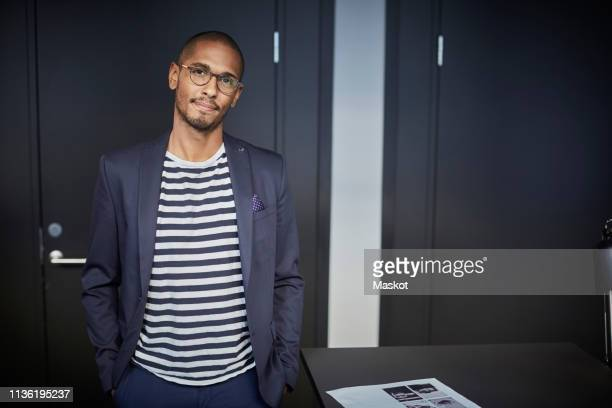 portrait of confident creative businessman standing in office - smart casual stock pictures, royalty-free photos & images