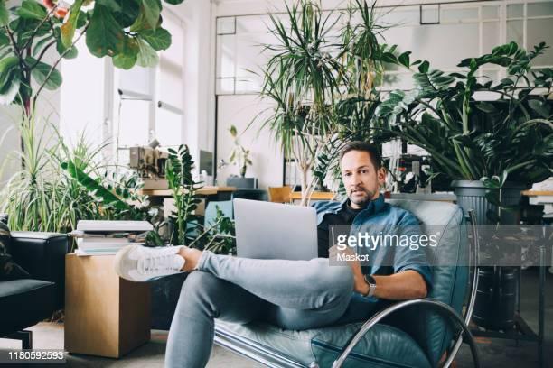 portrait of confident creative businessman with mobile phone and laptop sitting on seat in office - designer einrichtung stock-fotos und bilder