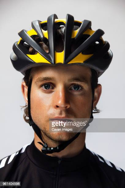 portrait of confident cyclist wearing helmet against white background - cycling helmet stock pictures, royalty-free photos & images