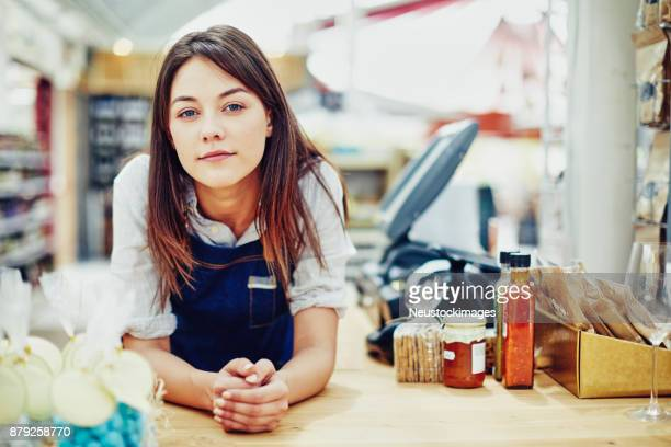 portrait of confident deli owner at checkout counter - convenience store counter stock photos and pictures