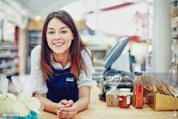 portrait of confident deli owner leaning on checkout counter - colletti bianchi foto e immagini stock