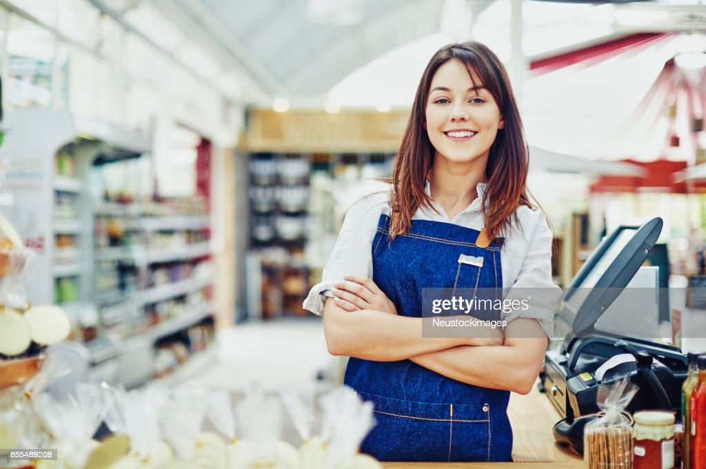 Portrait of confident deli owner standing at checkout counter : Stock Photo