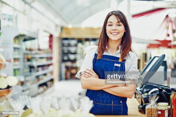 portrait of confident deli owner standing at checkout counter - convenience store stock photos and pictures